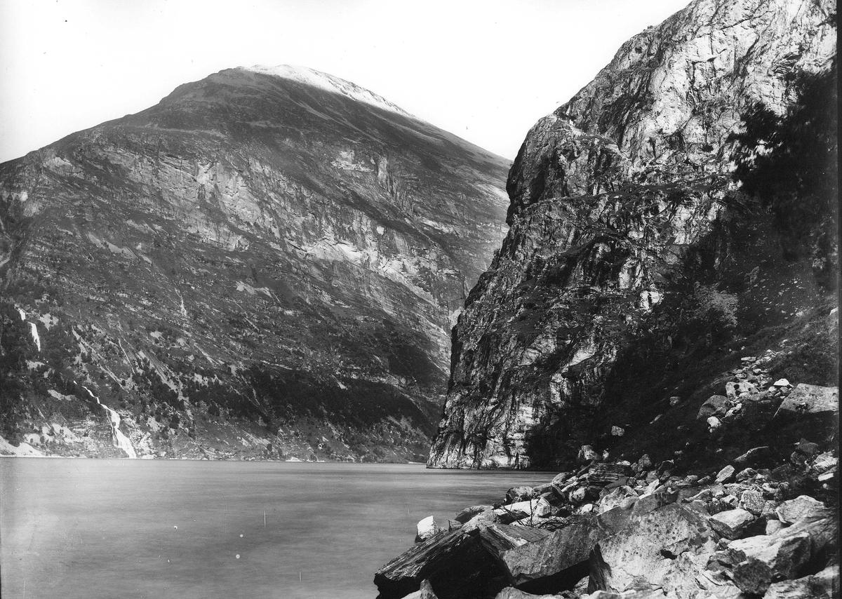 Landskap, ukjent sted. Bratte fjellpartier  går rett ned i fjord. Del av Den Norske Turistforenings samling landskapsbilder, de fleste tatt av fotografene Brødrene Brunskow.