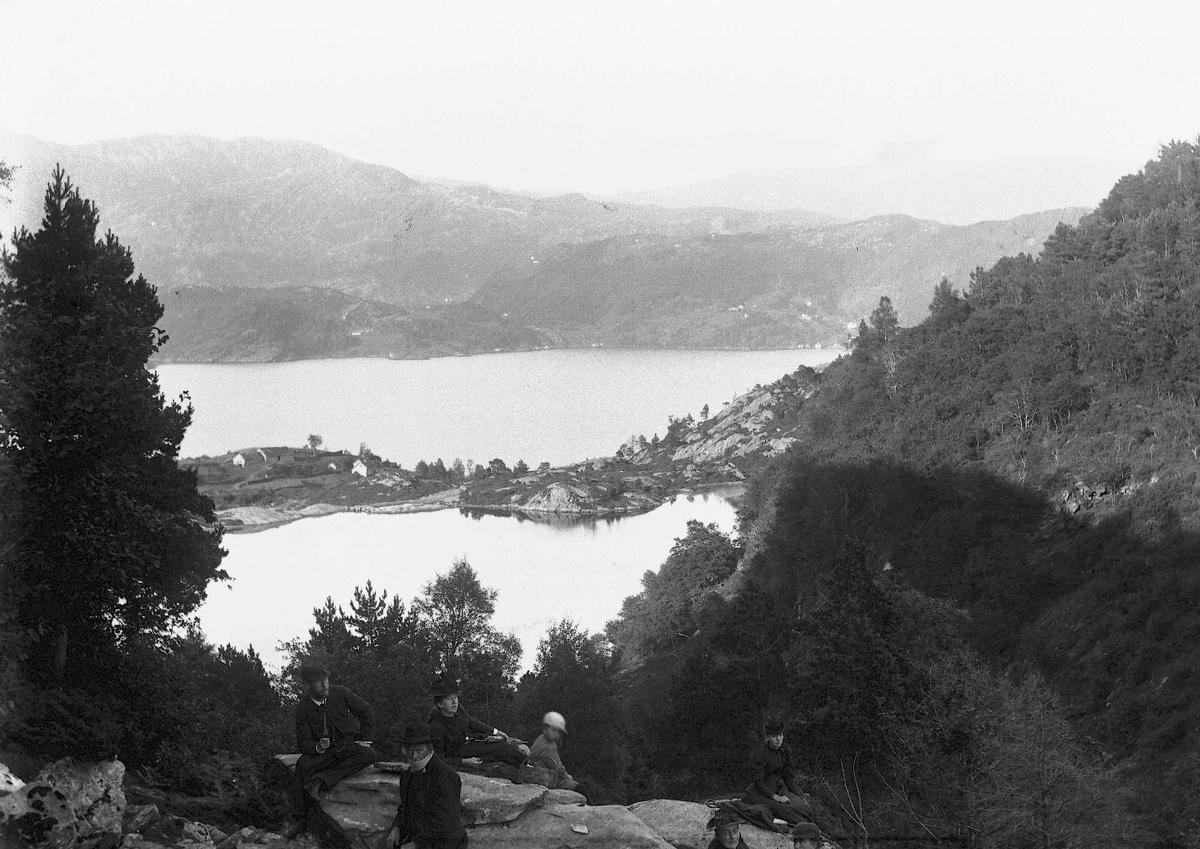 Fjell og fjord landskap med bebyggelse fra ukjent sted i Norge. En liten gruppe mennesker sees i forgrunnen.