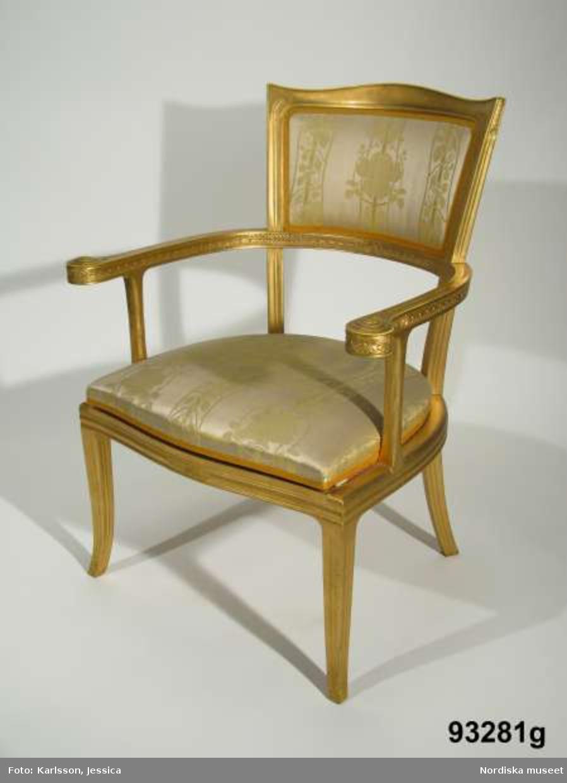 """Huvudliggaren: """"Möbel, 24 pjäser, utf. efter ritning av arkitekten F.[Ferdinand] Boberg för utställningen i Paris 1900. a-b två bord, c en soffa, d-k åtta länstolar, l-q sex små stolar, r-u fyra taburetter, v ett skåp, w en svänghylla och x en spegel.  Ink. 19/7 1902 Holmberg, J. E, herr, Sthlm."""""""