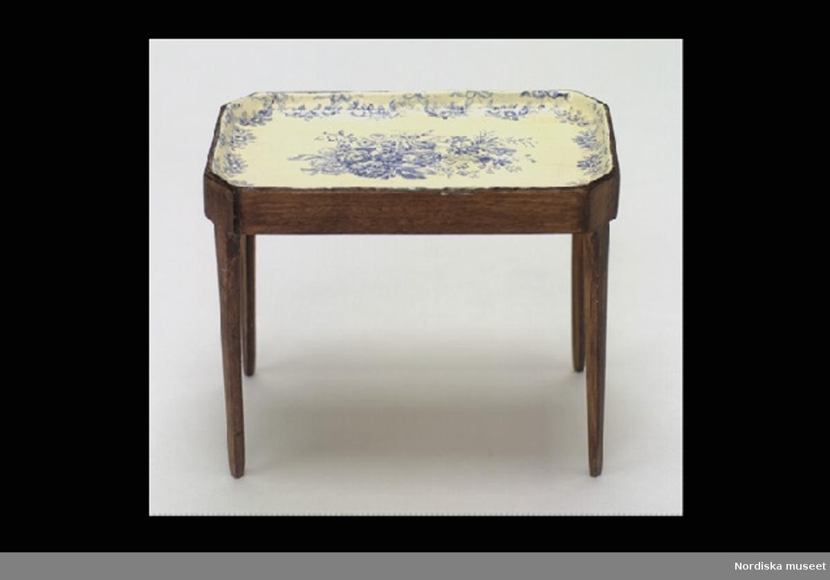 """Inventering Sesam 1996-1999: L 9   B 5,5   H 7,5 (cm) Tebord """"fajansbord"""", gustavianskt, till dockskåp. Underrede av brunbetsat trä, raka, nedåt avsmalnande ben. Bricka med höga kanter, imiterande fajansskiva, vitmålad med blå blomsterdekor. Tillhör dockskåp inv. 298.529. (Biblioteket) Berith Bergström, Stockholm, ritade och tillverkade dockskåpsinventarier från 1930-tal till 1960-tal under namnet """"Nolbyn"""". Bergström hade en affär """"Värmländskt hantverk"""" på Sibyllegatan, Stockholm. Föremålen är tillverkade efter svenska förebilder i skala 1:10. Dockskåpet brukat av systrarna Christina (f 1948) och Margareta (f 1949) Hofman-Bang i Djursholm, döttrar till givarinnan. Bilaga; uppgifter om tillverkaren. Birgitta Martinius 1997"""