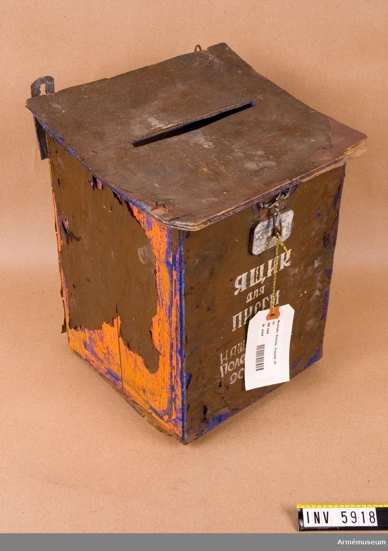 """Av plywood (kryssfanér). Mått 200 x 200 x 300 mm. Blå, brun och orange. Text på framsidan: Jasjtjik dlja pnsem nam adres polevaja posta 90655. Översatt till svenska (vissa bokstäver otydliga): Låda avsedd för - vår fältpostadress 90655. Gåva av S Tersmeden. Efter andra världskriget tvingades Finland arrendera ut Porkala till Sovjetunionen på 50 år. Det återlämnades till Finland år 1955. Text på baksidan av bifogat visitkort: """"Från Porkala vid återlämnandet två - tre dagar efteråt. 1955. Anders Grafström + givaren""""."""