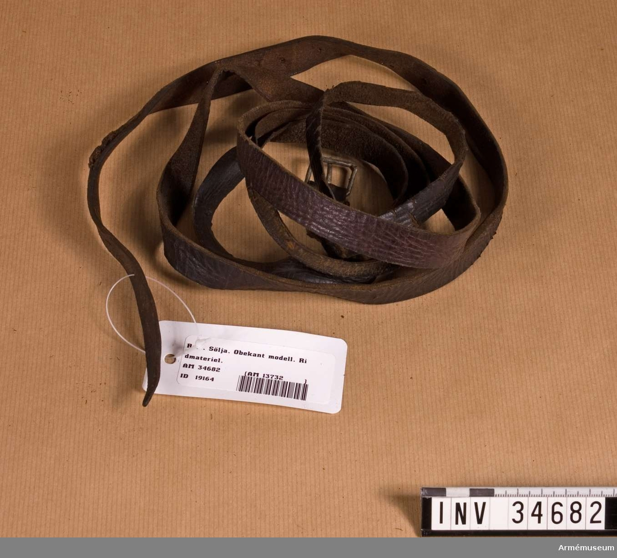 Samhörande gåva: 34682-91, remmar. Rem med sölja. Grupp K I. Obekant modell.