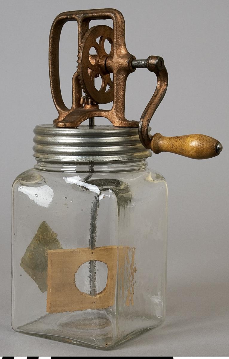 Smörkärna: behållare A, vispaggregat B. Smörkärna med vätskebehållare av glas, lock av aluminium, vevmekanism av gjutjärn, vev och visp av trä. Vevmekanismen bronserad, men är nött. Kärl: 116 x 117 mm. Mängd vätska: c:a 2 liter.