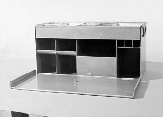Kassalåda eller kassaskrin avsedd för större postanvisningskassor. Framsidan nedfällbar. Inrett med fack för sedlar och kredithandlingar. Ovan ett löstagbart fack för växelmynt.  Kassalådan finns avbildad under artikelnummer 641.30 i Inventarieförteckningen år 1961.