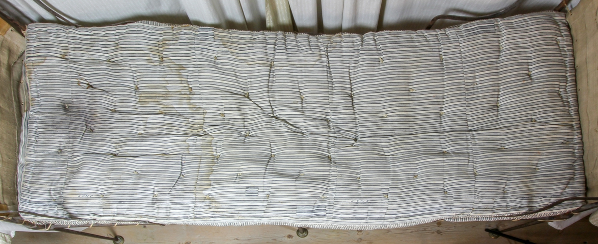 Madrass, tillverkad av troligen handvävt linnetyg, spetskypert. Varp randig i blått och vitt, inslag vitt. Puskor knutna av en ensam hamptråd.  Märkt med blå tråd: S C N 6 på två ställen.  Fyllning: gräs.