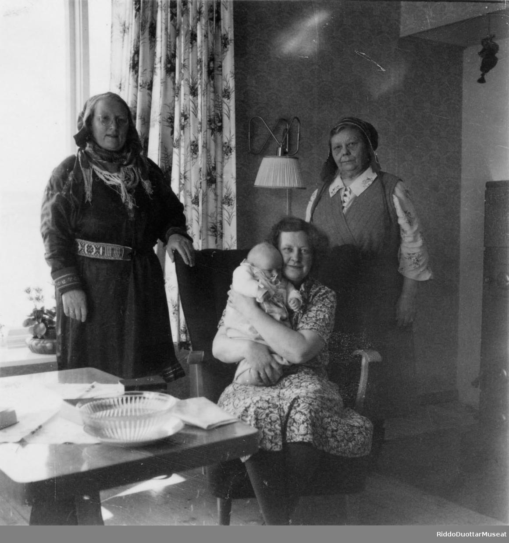 Nissonolmmoš cohka stuolus mánáin, guokte nissonolbmo duogábealde. En dame sitter på en stol med ett barn i fanget, to damer står bak. Heikka-Elle, Jortamor Máret ja Oddveig Harr