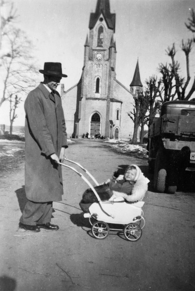 Organist Bjørn Somdalen med Grethe-Sofie i vogna  foran Kragerø kirke.  vinter/vår 1947/48.