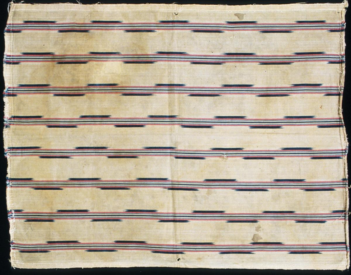 """Bolstervarsrandigt kuddstycke med flamfärgsmönster vävt i oliksidig spetskypert. Har varit fram- eller bakstycke på en kudde. Beige botten med ränder i varpriktningen (varpeffekt); enfärgade ränder i rött, mellanblått, mörkblått, beige och vitt samt flamränder i blå-vitt. Stadkant i ena sidan, de andra sidorna är kastade. Varp i 1-trådigt z-spunnet garn, troligen bomullsgarn, 42 trådar/cm. Inslag i halvblekt 1-trådigt z-spunnet lingarn, 28 inslag/cm. Rester av dun på baksidan. Vidhängande märklapp med texten: """"H.58."""". Jämför med inv.nr 906."""