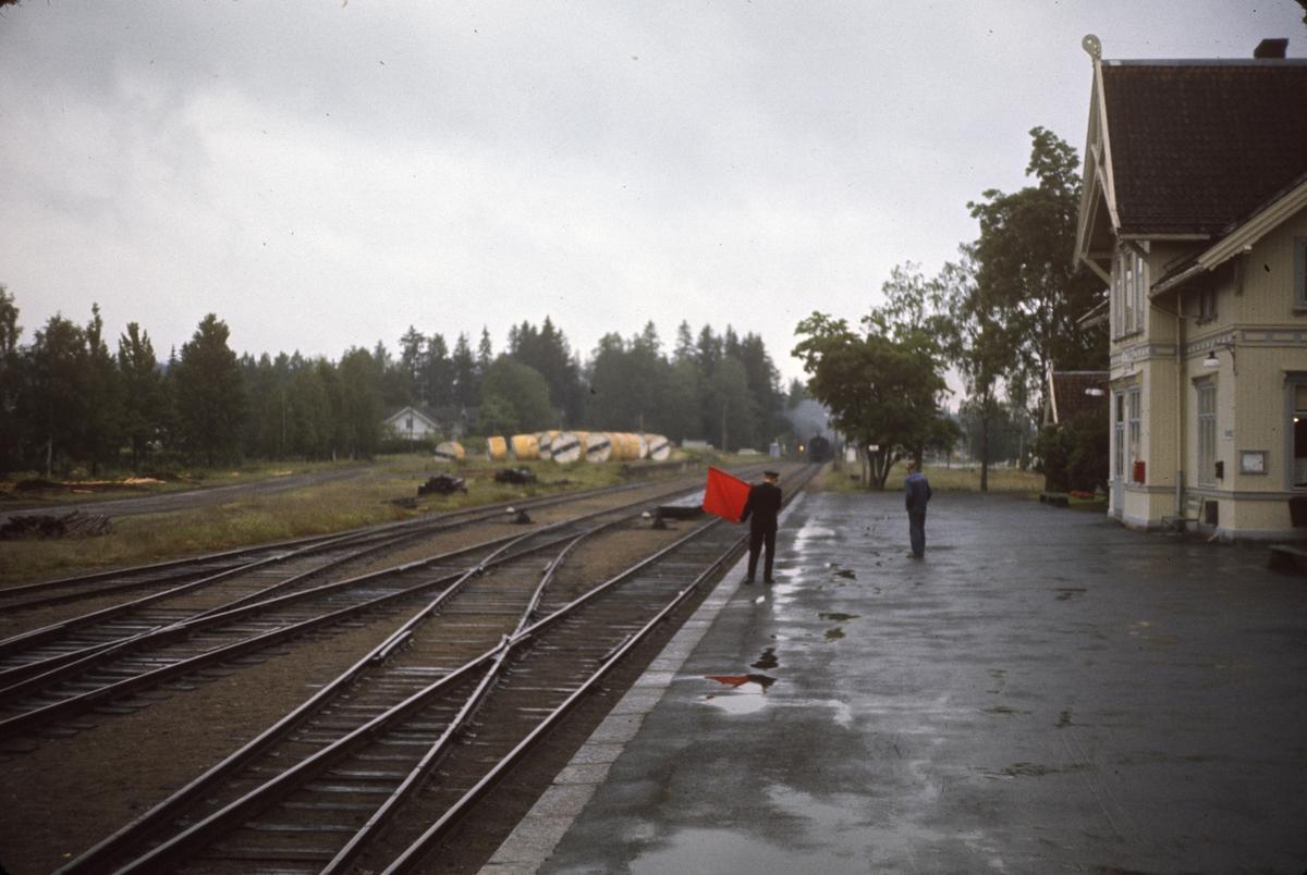 Godstog på Solørbanen nærmer seg Roverud stasjon. Toget trekkes av damplok 26c nr. 433. Togekspeditøren viser stoppsignal.