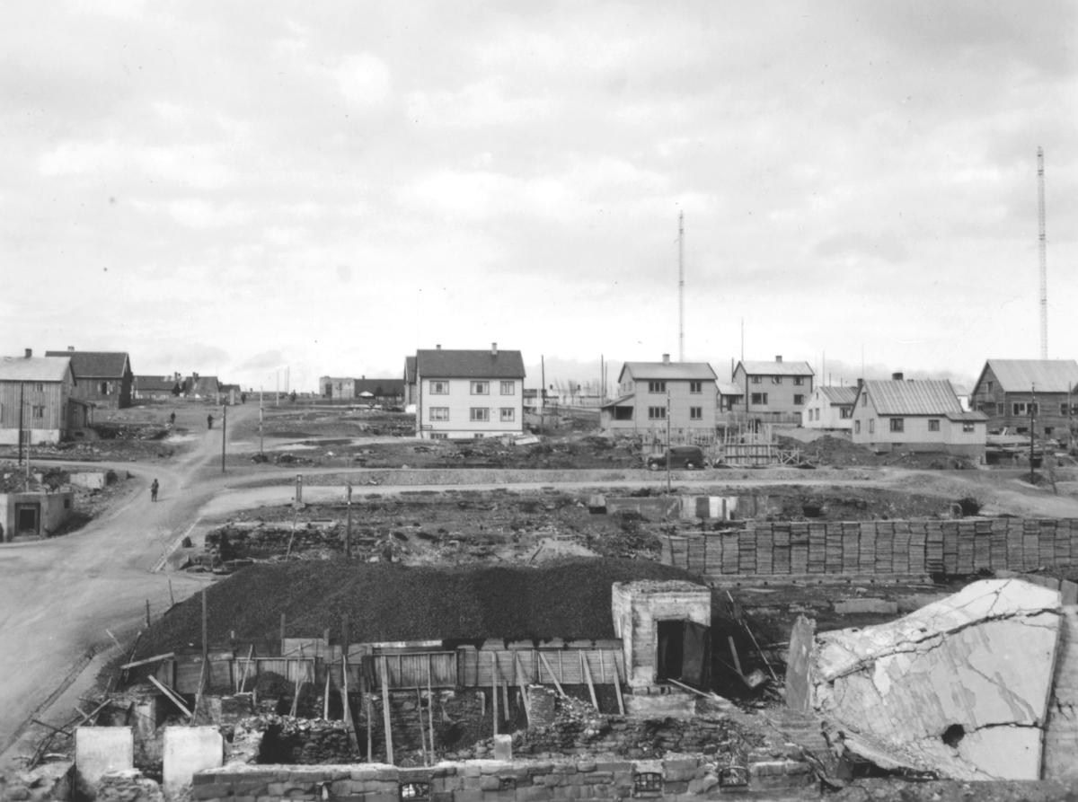 Motiv fra gjenreisningstiden i Vadsø etter andre verdenskrig. På bildet ser man flere nyoppsatte boliger. Nedenfor husene er det en stor ledig tomt. De to høye radiomastene til Vadsø Kringkaster ses mot himmelen