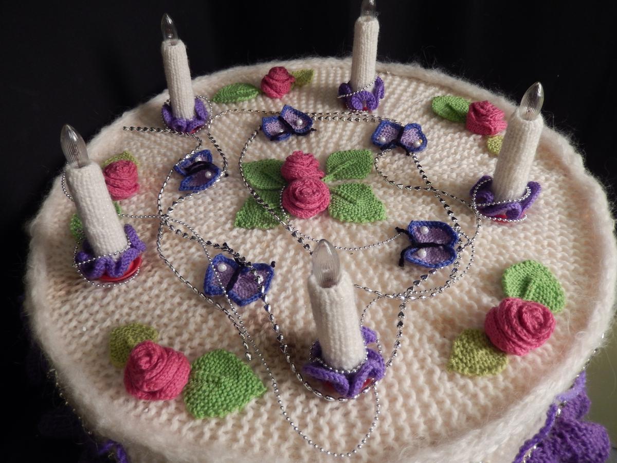 """Kaken er strikket av en dame fra husflidslaget i forbindelse av kvinnemuseets utstilling 2010 """"strikke strikke sa kjærringa"""" Kaka er rundstrikket i hvitt garn pyntet med lilla rundkappe nederst. Oppå kaken er det feste til 5 lys som er lilla liten kappe nederst rundt hvert lys som er kledd med hvit strikk. Pyntet ellers med lilla strikkeblomstrer og røde blomstrer, grønne strikkete blader og pyntet ellers med sølvfarget kjeder."""