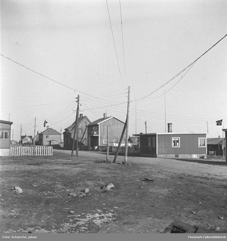 Et gateparti fra Damsveien i Vadsø. Bungalover. Den første bungaloven fra venstre hører til Torvald Berg og den andre til Gandola.  Fremst på bildet grusvei og to strømstolper.