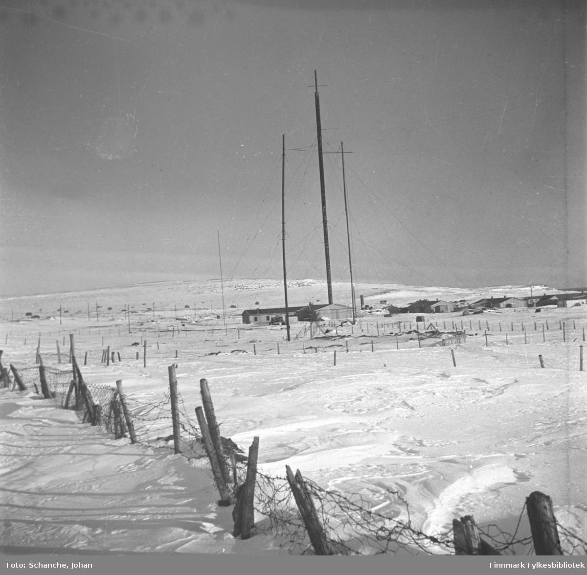 Radiomastene i Vadsø fotografert på vinter -46. Brakkehus. Kringkastingshus ble bombet natt til 3. juni 1940 og kringkasting hold hus i et brakkehus. Mastene står skjevt. Nederst på bildet piggtrådgjerde.