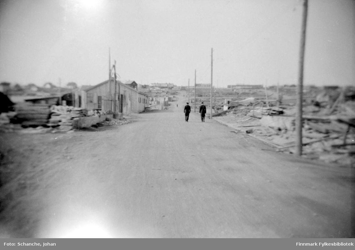 Ruiner i Vadsø -46. Bare grunnmuren står igjen av husene på begge sider av grusveien. Bak ruiner ligger Varangerfjorden. To menn går langs veien gjennom ruinene.  Gjenreisningsarbeid har begynt og brakker og andre byggninger blir reist opp her og der.
