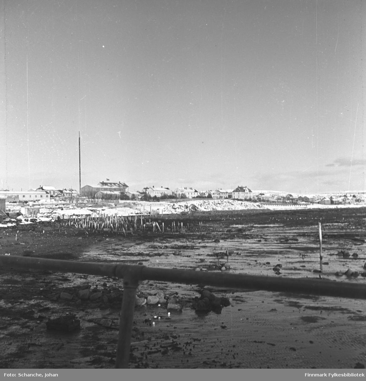 Vadsø by fotografert fra havn/kai. Foran på bildet fjæra og rester av et kai, lenger bak byggninger som sto igjen etter bombingen i Ytrebyen, bland dem (det første store hus fra venstre) kysthospitalet.