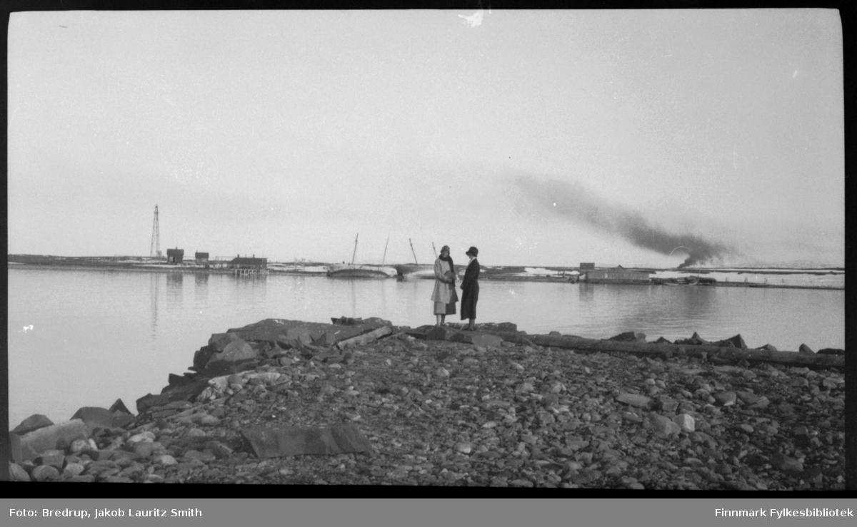 To kvinner i fine kåper og hatter fotografert på Ørtangen.  I bakgrunnen ser vi Vadsøya med luftskipsmasta og bygninger.  Tjukk røyk stiger opp fra øya til venstre for de to kvinnene.