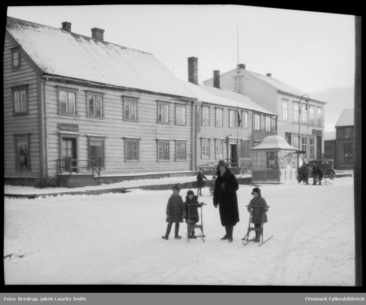 Vinterbilde fra torget i Vadsø.  Antakelig er kvinnen på bildet Hildur Bredrup, og noen av barna er Bredrup-barn.  De bruker spark.  I nærheten av kiosken en liten gruppe gutter og menn, og en bil står parkert.  Butikker og forretninger ved torget.