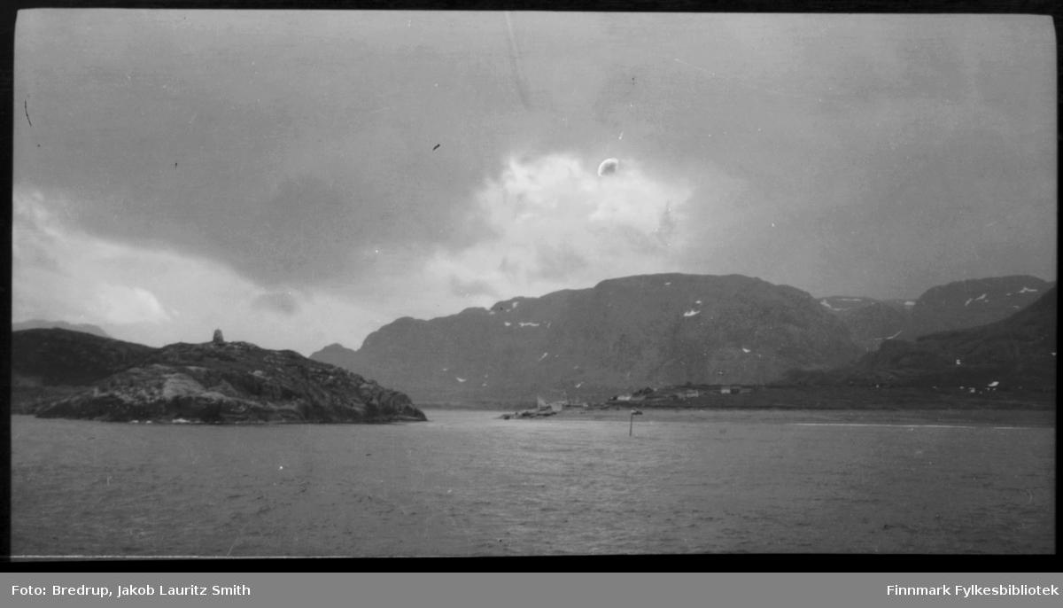 Grense Jakobselvs utløp i havet.  Et seilingsmerke til venstre for fotografen.  På den andre bredden ligger Russland, midt i elva et grensemerke.  Vi kan skimte bygninger og båter dratt opp på land på den andre siden.