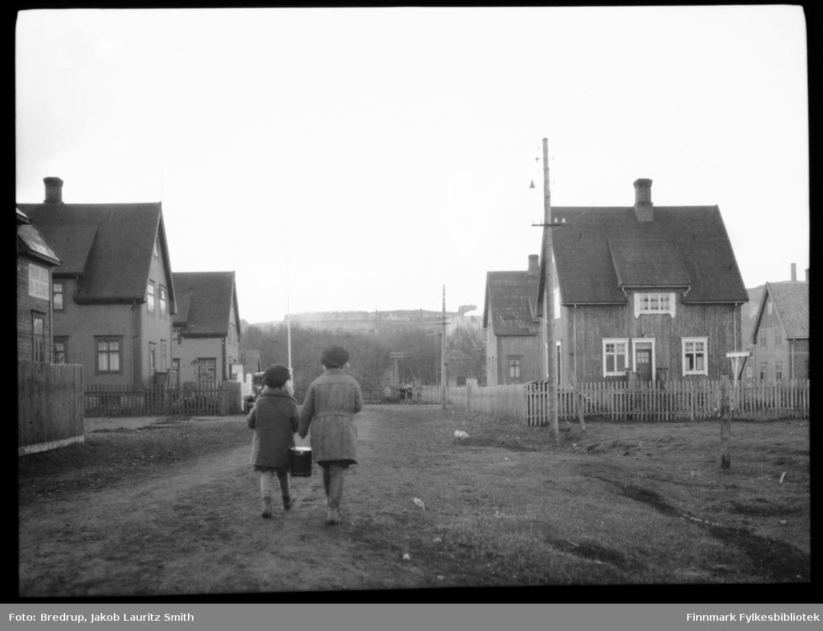 To jenter går nedover ei rett gate i Kirkenes.  Jentene bærer et spann, og de er fotografert bakfra.  I enden av gata venter andre barn.  I høyden over gata ligger A/S Sydvarangers anlegg.  Huset nærmest fotografen på venstre siden av veien har et skilt: 'Tannlæge Sv. Isachsen'.