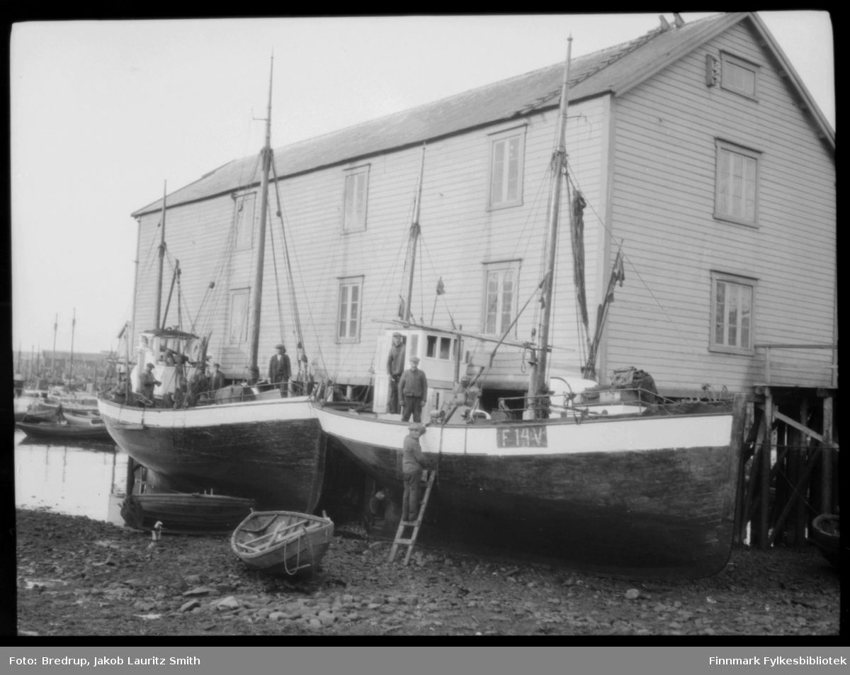 To store fiskefartøy trukket opp i fjæra ved ei kai, Valen i Vardø.  Båten nærmest kamera har kjennetegn F 14 V.  Mannskap ombord i båtene, lettbåtene ligger trukket opp ved siden av.  Antakelig er båtene trukket opp for stell og vedlikehold, skraping og maling.