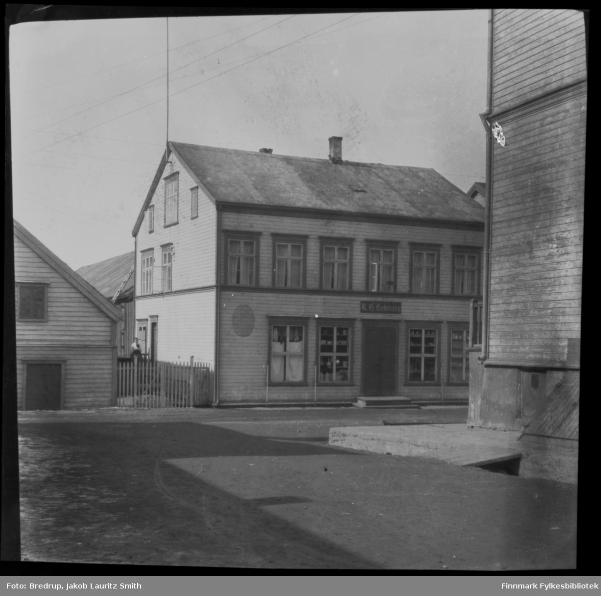 Butikk med skilt 'R. G. Esbensen' i Vadsø sentrum.  Utenfor bygningen står en kvinne. Vi ser gata og andre bygninger.