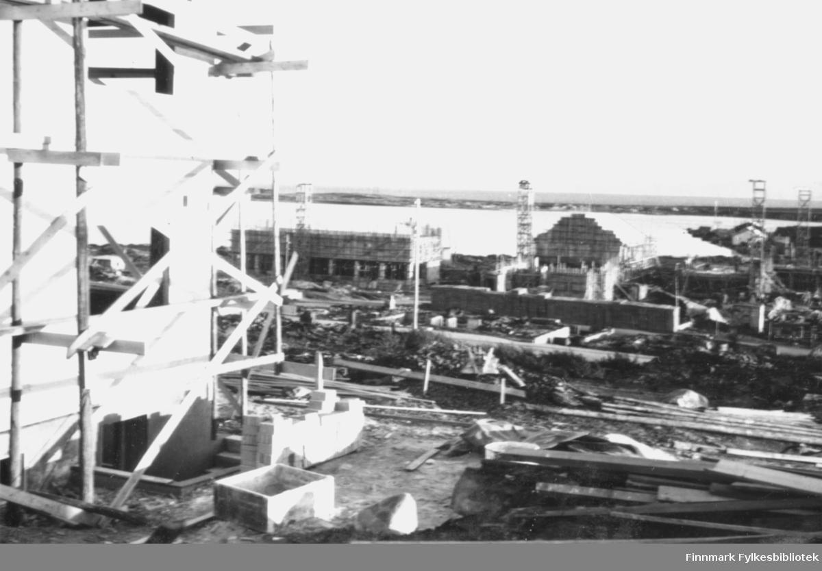 Gjenoppbygging av Vadsø sentrum etter andre verdenskrig. I forgrunnen til venstre i bildet står et hus under bygging med diverse byggematerialer rundt. I bakgrunnen ser man flere hus under oppbygging med stillaser rundt, og forskallinger til bygging av piper står flere steder i området. Utsikt mot havet og Vadsøya