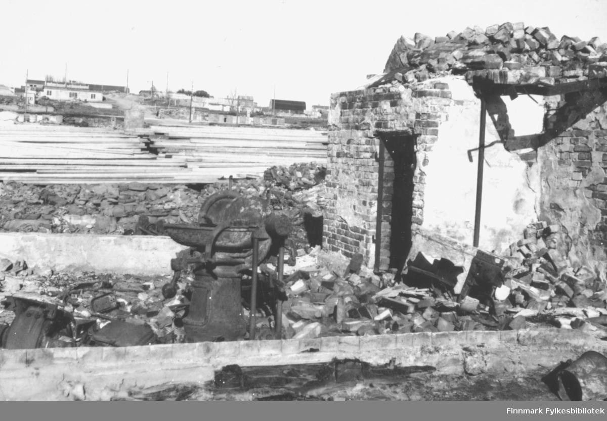 Ruinene av et hus i Vadsø sentrum høsten 1946. I bakgrunnen ligger hauger med planker som skulle brukes til gjenoppbyggingen av alle husene som ble bombet under andre verdenskrig. Bak disse haugene med materialer ser man flere hus og/eller brakker, samt stolper med elektrisitetslinjer imellom