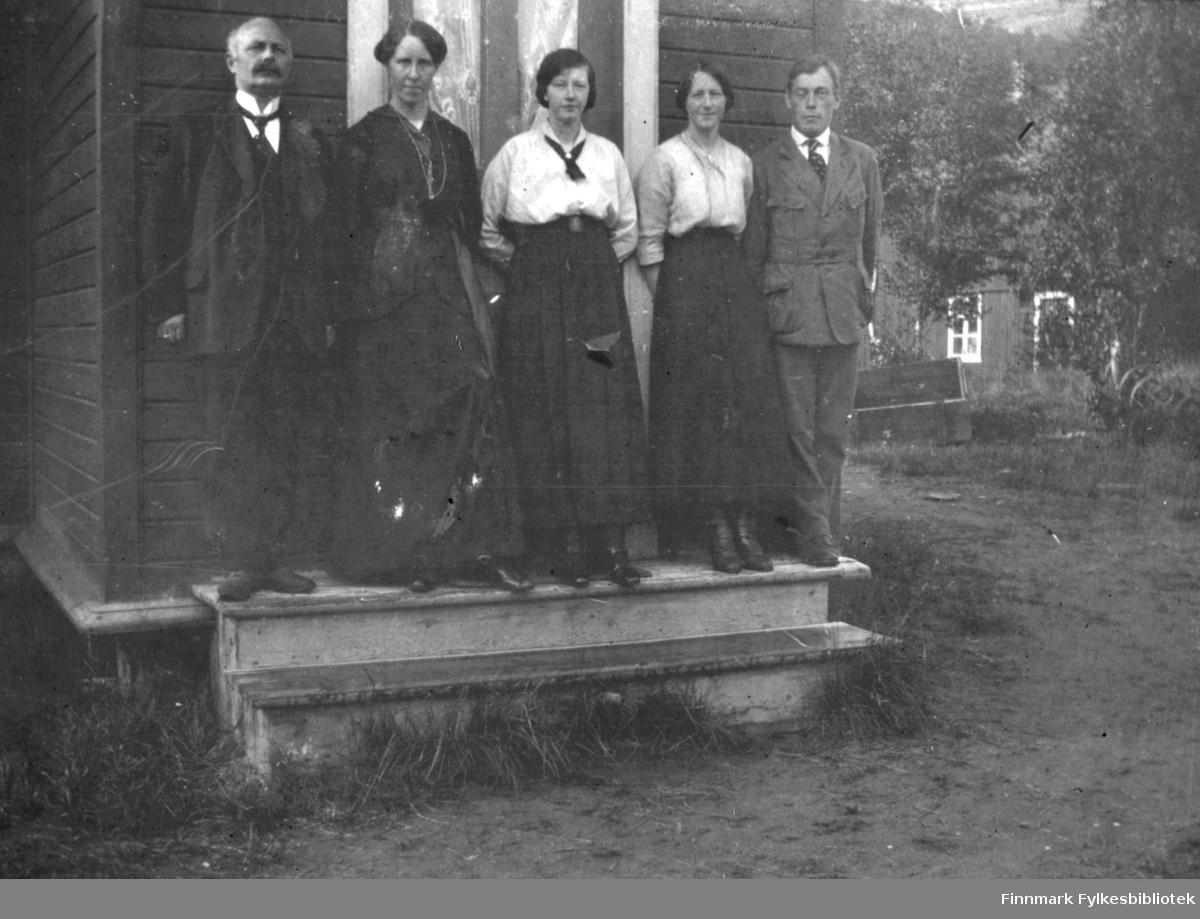 Tre damer og to menn fotografert på trappen utenfor et hus i Rassejåkka i Tana en sommerdag i August 1916. Alle fem har på seg fine klær. I bakgrunnen kan man se en annen bygning mellom trærne.