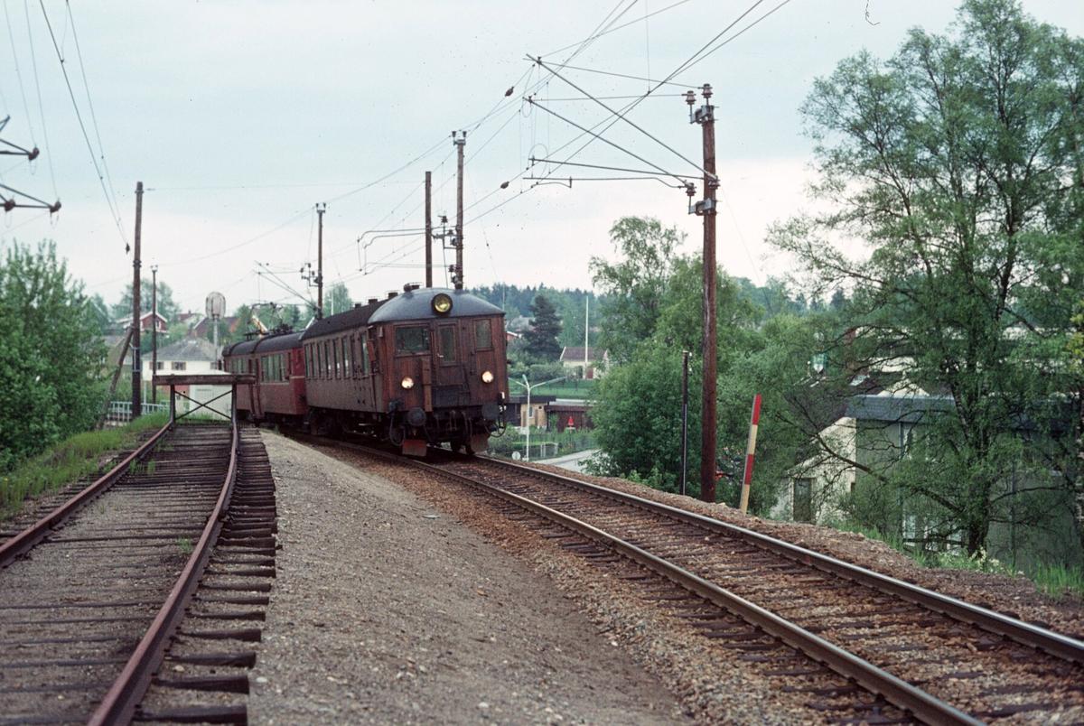 """Persontog fra Østfoldbanen Østre linje kjører inn på Ski stasjon. Motorvognsett type 65 med styrevogn """"ubåt"""" BFS 65 og motorvogn BM 65B 31."""