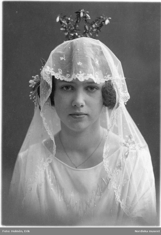 Porträtt av en brud i brudklänning, slöja och krona.