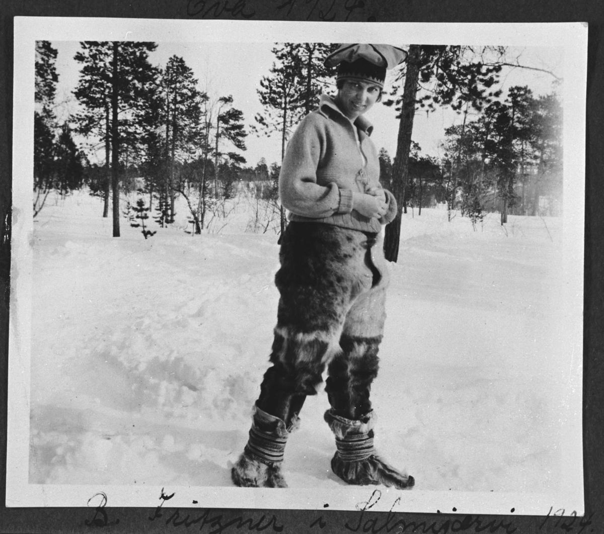 Ung samejente fotografert på vinter i Salmijärvi. Hun har på seg reinskinnbukse, genser og samehua.