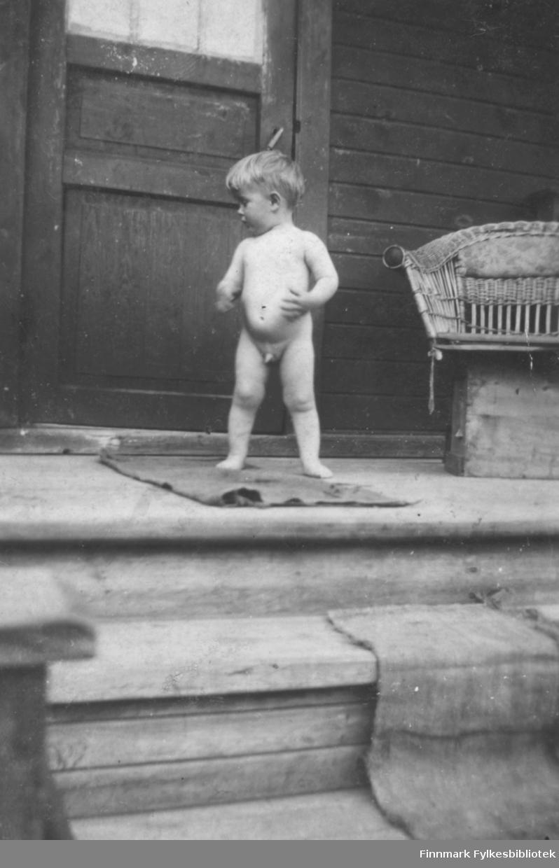 Harry Rognlid, ca. 1 år gammel, står helt naken på en trapp utendørs. Det må ha vært en fin sommerdag. I bakgrunnen en kurvstol