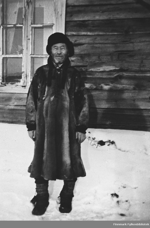 Andreas Falk, også kjent som Mikkel-Antti i bygda, antagelig fotografert foran huset sitt,  Tidsperiode: ca. 1910. Andreas Falk var skomaker i Vestre Jakobselv. Han står ved husveggen kledd i pesk og skinnlue.