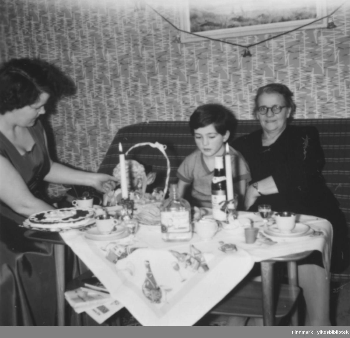 Julekaffe hos familien Ebeltoft, ca. 1953. Fra venstre: Ragnhild og Torill Ebeltoft, Svanhild Kvam. På bordet nisseduk og stearinglys