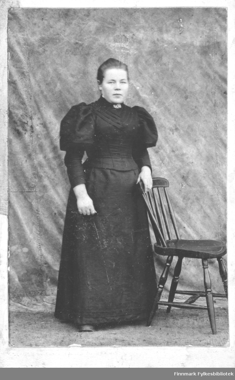 """En kvinneportrett montert på lys rosa kartong. Kvinnen er Anna Særvold,  født 24.06.1876 i Vadsø. Hun er gift med Oluf Særvold, fisker,  født 14.04.1874 i Rødø, Helgeland. Bak bildets kartong er det notert """"Fra Anna til Nanna Balo"""".  Fotografen er ukjent. Anna er kledt i en svart kjole,med bluseliv med puffermer og et langt svart skjørt. I halsen har hun en liten nål.  Bildet er tatt med en litt provisorisk bakgrunn, kanskje et seil fra en båt og en pinnestol - og kjolen kan være brudekjole, sort brudekjole var vanlig på den tiden. I albumet er det skrevet Servold, istedet for Særvold. Nanna Evida Bergitte Vara, født Balo (født 09.10.1878) er sannsynligvis den personen som Anna har dedikert bildet til. Nanna var gift med Paul Rudolf Vara, som drev med fiskeri.   I folketelling for 1900 i Vadsø er hun registrert på adresse Thomas von Westensgade 4, 2.etasje. I 1900 har de en sønn, Casper Særvold, født  05.06.1900. I folketellingen for 1910 er de flyttet til Vardø og bor i Kristian 4des gate 119. De er da registrert med 3 sønner, Odin (født 10.08.1901), Hans Herman (20.03.1905) og Gunnar (31.01.1909) Særvold. Anna er da registrert som Anna Lovise Særvold, fiskers hustru. Anna Lovise er registrert på sykehuset i Vadsø i 1910 """"pasient paa sygehuset"""". Hvor det det er blitt av Casper Særvold vites ikke. Gunnar Særvold er i 1910 """"bortsat til forpleining"""", han er da 1 år, mens Hans Særvold også er """"pasient på Sygehuset""""."""