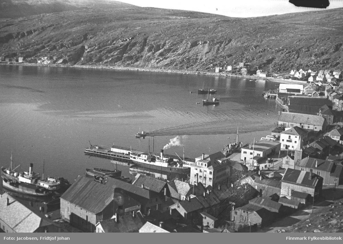Deler av Hammerfest sentrum og Molla fotografert fra fjellet Salen. En del hus og forretningsbygg står langs strandkanten. Et par kaier stikker ut i sjøen nede til venstre på bildet. Kaia til høyre, omtrent midt på bildet, er Hauan-kaia. Litt av bydelen Molla med Hamran ses ved foten av Mollafjell oppe til høyre på bildet. Noen båter ligger fortøyd i havna og noen ligger ved kaiene. Oppe til venstre ligger deler av Fuglenesfjell og ved foten av fjellet ligger noen hus langs Fuglenesveien.