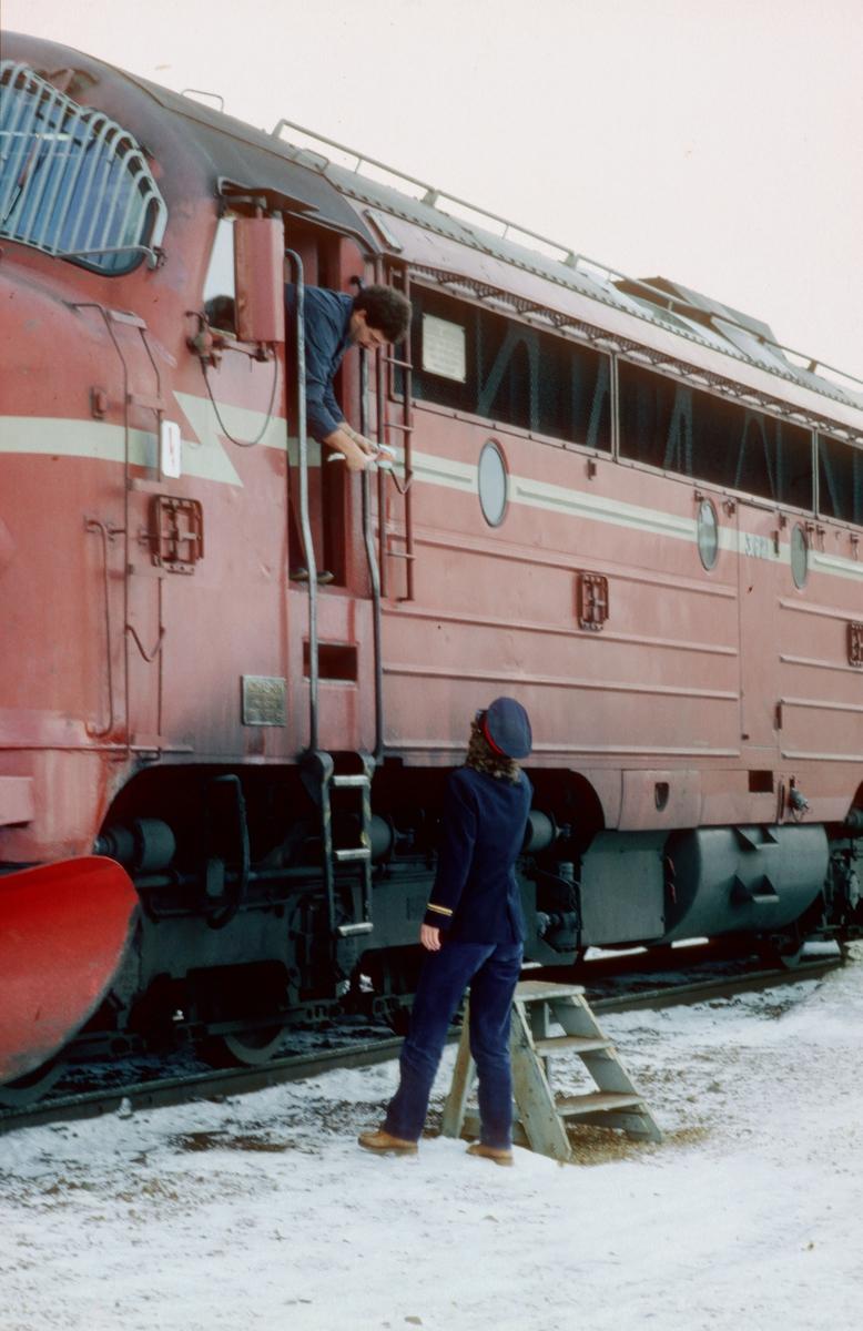 Togekspeditøren på Brekkvasselv stasjon overleverer ordre til lokomotivføreren i et godstog.