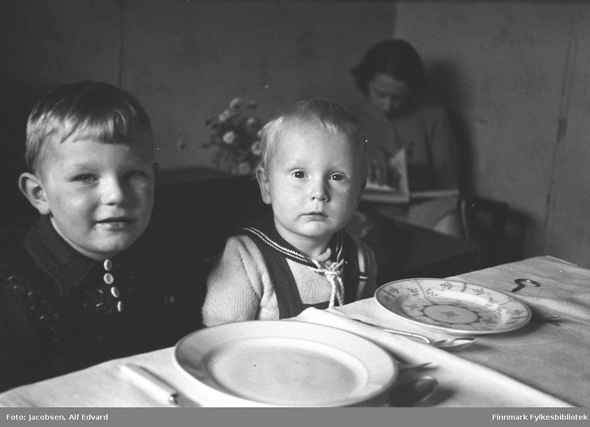 To små gutter sitter ved et bord. Det er fetterene Åge Christian Jacobsen til venstre og Arne Jacobsen. I bakgrunnen sitter Aase Jacobsen, mor til Arne. Åge har en mørk jakke med krage og lys knapper i halsen. Arne har en lys/hvit genser med mørk krage og snorer i halsen. Selene på en snekkerbukse går over skuldrene hans. Det er en hvit/lys duk på bordet og oppå står to tallerkener, den ene hvit og den andre med stråmønster. Noe bestikk ligger også ved siden av. Stolene de sitter i har mørke rygger og armlener. Aase har en ganske lys kjole på seg og sitter og blar i en bok. På bordet ved siden av henne står en blomsterbukett.