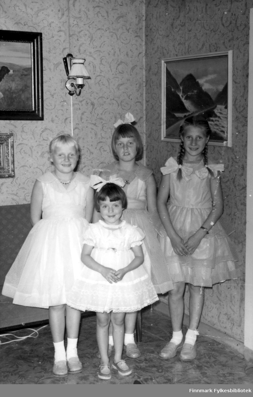 Fire kusiner poserer med sine nye finkjoler i en stue. Fra Venstre til høyre: søstrene Reidun Stock og Ruth Stock. Ved siden av står Elin Rushfeldt og i forgrunnen ser man Svanhild Rushfeldt. Kjolestoffet er blitt sendt fra familie i Amerika. Kjolene var ferdigsydde (unntatt Svanhilds, som var kjøpt) og bildet skulle senere sendes tilbake til familien i Amerika. Jentene står i et rum med tapet på veggen og det er hengt opp tre bilder. Bak jentene står en sofa og en lampe henger på veggen. Kusineflokken har pyntet seg til annledningen med smykker og hårsløyfer.