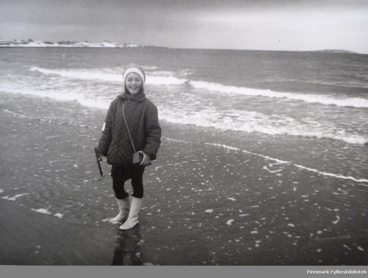 Svanhild Rushfeldt er på stranda med Krampenes i bakgrunnen. Havet bølger bak henne og hun er godt kledd i en tykk jakke og støvler. På seg har hun også en lue, og over skulderen henger en liten veske.