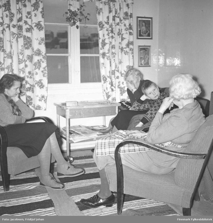 Arne Jacobsen med sin mor, farmor og farmors søster. Bildet er sannsynligvis tatt i huset til familien i Hammerfest i 1953-1955. På venstre side sitter Aase Randi Jacobsen, til høyre fremst på bildet sitter Olga Jacobsen, Arne Jacobsen i midten kikker på fotografen, og Pauline Jacobsen sitter ved vinduet. Alle damene har skjørt/kjoler på seg og Olga har i tillegg et rutet forkle. Arne har en mønstret genser på seg. Et lite bord står ved vinduet med aviser/tidsskrifter liggende under. Stua har blomstrete gardiner og to innrammede fotografier henger på veggen over hodet på Pauline. To matteryer ligger på gulvet der de sitter. Bebyggelsen som ses gjennom vinduet kan være Nedre Rairo med et islagt Storvann mellom.