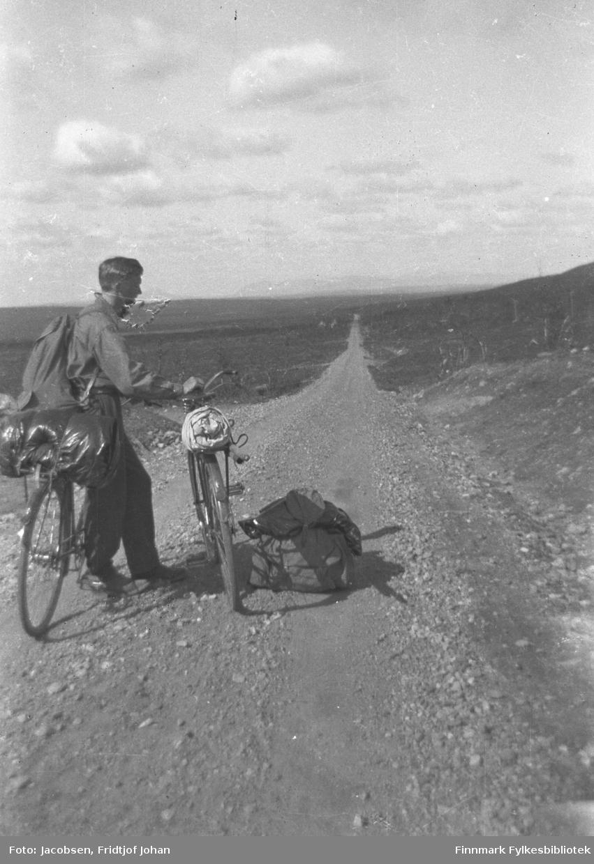Fridtjof Jacobsen på sykkeltur på Sennalandet på vei mot Alta. Grusveien, som i dag er E6, er ganske smal og gruslagt. Terrenget rundt er flatt med gress- og lyngdekke. Noen små trær og busker ses også. Han lener seg mot sykkelen sin, som har en stor mørk sekk spent fast i bagasjebrettet, mens han holder en annen sykkel. Han bærer på en ryggsekk og en annen ryggsekk står på veien ved siden av sykkelen.