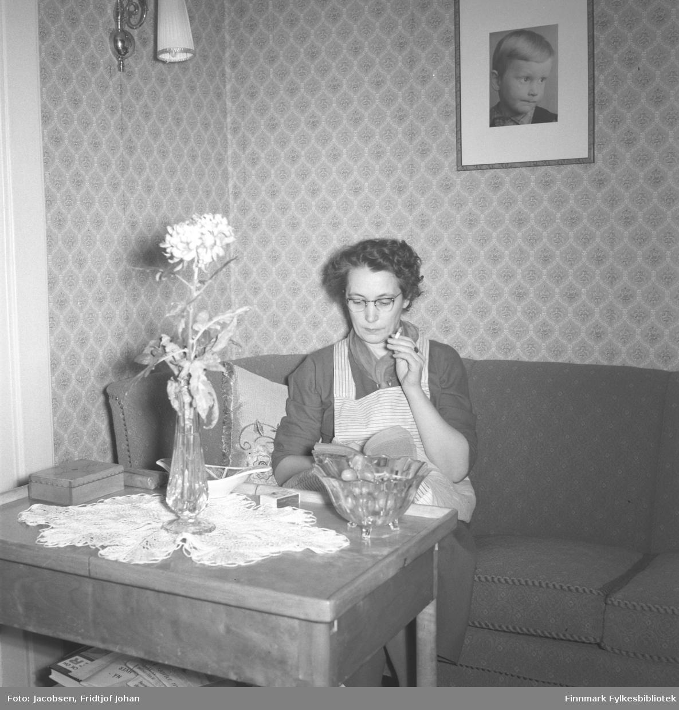 Aase Jacobsen tar seg en røyk mens hun leser bok. Hun har en mørk kjole og et lyst, stripet forkle på seg. På veggen bak henne henger et bilde av sønnen Arne. Foran henne står et lite bord med en blomstervase, en skål, en fyrstikkeske og en heklet duk oppå. En lampe henger oppe til venstre og en liten del av en gardin ses ved siden av. Bildet er tatt i hennes hjem i Storvannsveien.