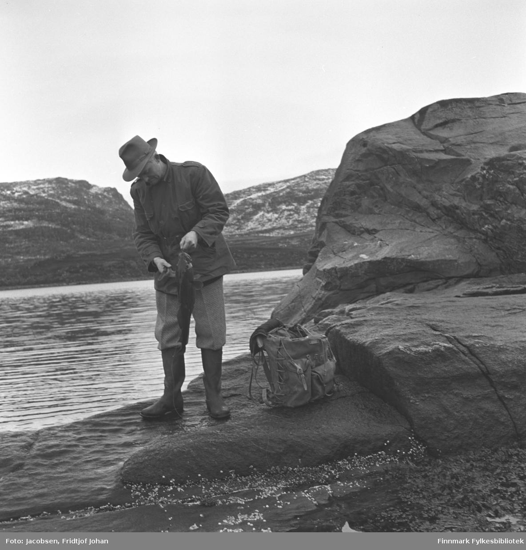 Fridtjof Jacobsen holder opp en fisk som han har fanget