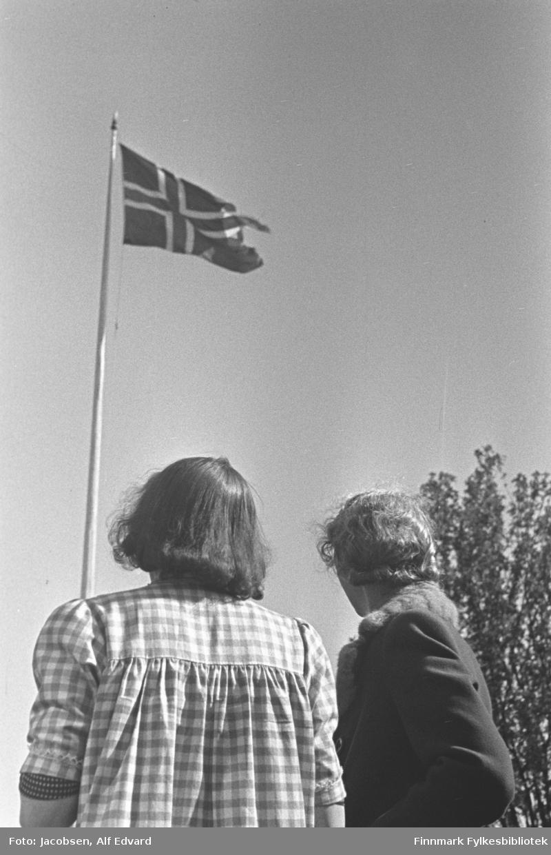 Aase og Ingeborg Jacobsen stående med ryggen til fotografen. De ser opp på det norske flagg som henger i toppen av en flaggstang. Aase, til venstre på bildet, har en rutet sommerkjole på seg. Ingeborg er iført en mørk kåpe/jakke. Helt til høyre på bildet ses et tre med mye løv på. Det er blå himmel og flagget vaier litt i vinden. Iflg. giver av bildet kan det være tatt i mai 1945 på Lødingen.