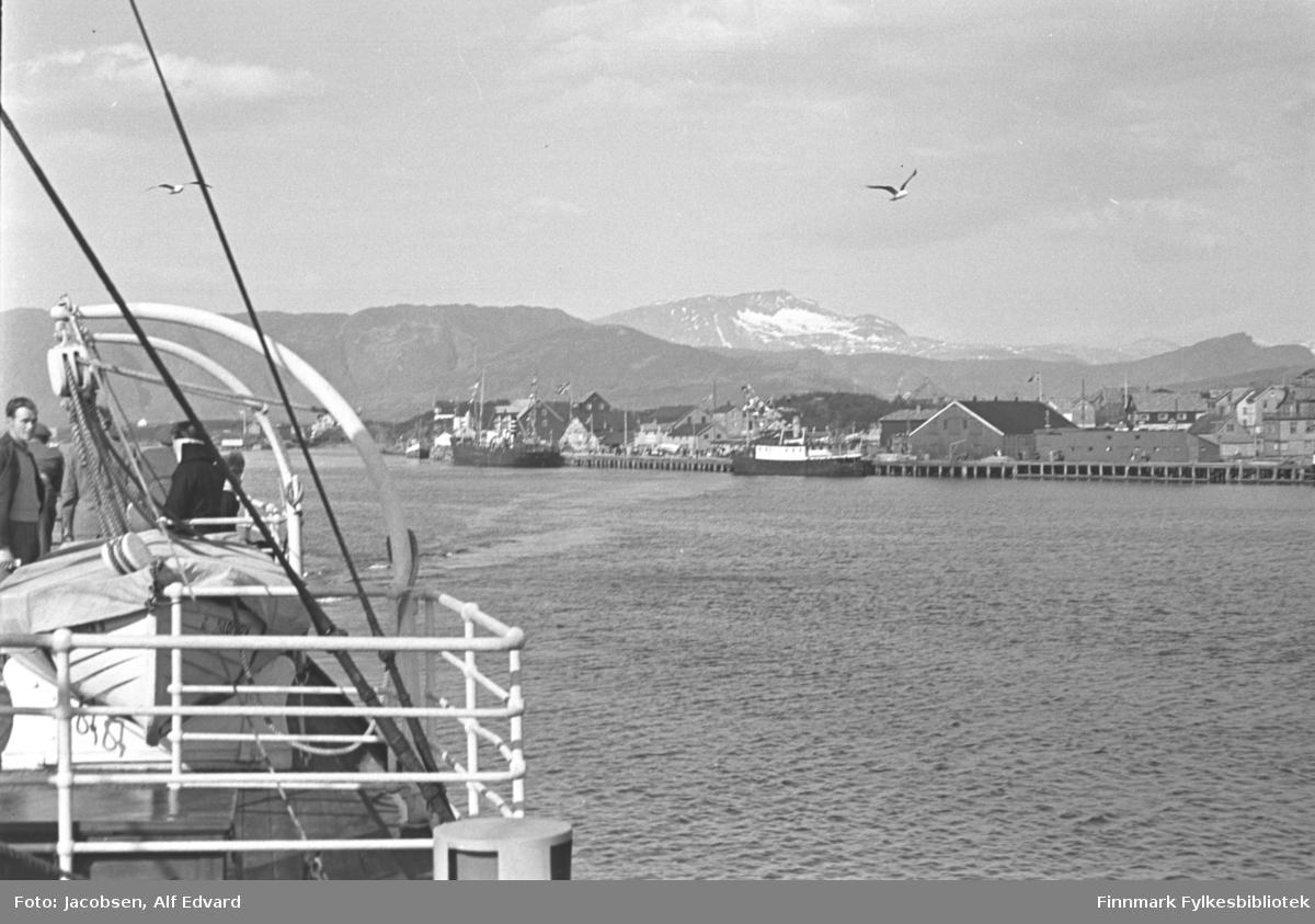 """Bilde tatt fra Hurtigruteskipet DS """"Lofoten"""" inn mot land. Iflg. informanten kan stedet kan være Tromsø. Noen personer står oppe på dekket ved en livbåt. Et hvitmalt metallrekkverk er nærmest kamera. Toppen på en ventil og noe tauverk ses også. To måker ses mot den blå himmelen. Mange store bygninger står oppå en lang kai. En skøyte, en større mørk båt og det som kan se ut som en ferge ligger inntil kaia. Et høyt fjell ses i horisonten og bak det ses toppen på et annet fjell. Det har snøflekker eller en isbre på toppen. Små bølger på sjøen vitner om lite vind på en fin sommer- eller tidlig vårdag."""