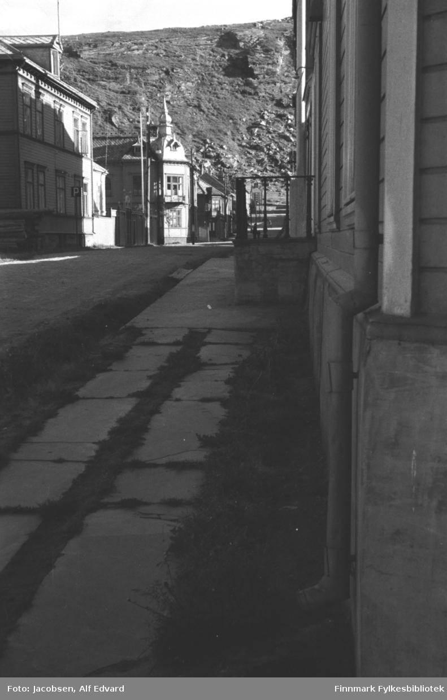 Bilde tatt nederst i Storgaten mot fjellet Salen. Gaten er en ganske bred grusvei. Steinheller ligger i to rader med litt gress voksende rundt og mellom dem. Bygget til høyre med ganske lyst, liggende panel er Norges Bank. En trapp med mørkt rekkverk står midt på langsiden. Et grått takrenne-nedløp på veggen nærmest kamera. På andre siden av gaten står et stort bygg med lyst, liggende panel og flere vinduer på langsiden. Det er muligens Nissen-gården. Et parkeringsskilt står på fortauet utenfor. Bygget har en ark og skiferdekke på taket. Bygg nr. to på venstre side er Finckenhagen. Det er også ganske lyst, har mange vinduer både på hjørnet og langsiden. Bygget har en ark og skifertaket og på hjørnet står en løkkuppel. Videre oppover gata står flere store bygg. Nærmest Finckenhagen er apoteket, så Sparebanken og deretter posten. Flere el-stolper står på venstre side av gata. Salen har litt vegetasjon, men mye stein/berg vises også.