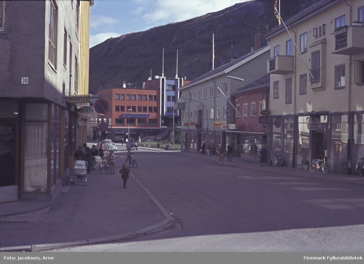 Liten del av Hammerfest sentrum. Gata er Kirkegata som går over i Strandgata. Kryssende gate, helt nederst er Storgata. På hjørnet med et 30-tall på veggen er Gardinhuset - Brødrene Hansen og Madelene blomsterforretning nedenfor med Torvkiosken vegg i vegg. På høyre side av veien ligger Finnmark Dagblad, Wulff med bl.a garn, broderi og G. Hagen bok, papir og musikk. I enden av gata står DnC-bygget med parken Ole Olsens plass foran. Fjellet i bakgrunnen er Salen. Noen få biler ses i nedre del av gata og mennesker, noen med sykler og barnevogner, går langs fortauene.