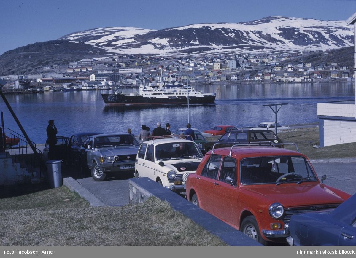 """Hurtigruta M/S """"Finnmarken"""" på tur ut fra Hammerfest en tidlig sommerdag med havblikk. Bildet er tatt utenfor Hammerfest kirke og trappa til venstre går opp til presteboligen. Biler står parkert oppover langs fortauet ved kirka og nede langs Sørøygata. En liten gruppe mennesker står ved bilene. På andre siden av fjorden er bydelen Fuglenes. Rett ovenfor baugen til Hurtigruta ligger bl.a Hammerfest videregående skole og Fuglenes skole. Sykehuset og Søsterhjemmet ses over akterenden på Hurtigruta med røstveggene mot. Noe snø ligger enda igjen på fjellene Storfjellet og Vedhammeren. Til venstre ses Kullkrana, lenge et landemerke på Fuglenes. Noen båter ligger langs kaiene på Fuglenes."""