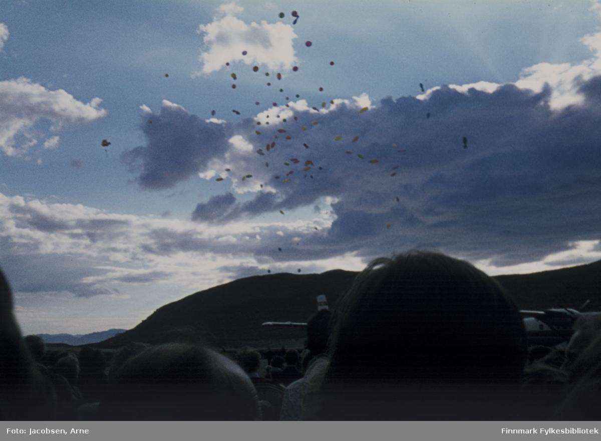 Ballongslipp over Hammerfest lufthavn. Flyplassen er akkurat offisielt åpnet av daværende samferdselsminister Annemarie Lorentzen. Ballongene vises mot en delvis skyet himmel. Nederst i bildet vises en liten del av folkemengden som hadde møtt opp. Delvis skult av hoder ser vi Twin Otter-fly fra Widerøes flyveselskap stå parkert på rullebanen. Fjellet i bakgrunnen er Vardfjellet og en liten del av Sørøya kan ses mot foten av Vardfjell.